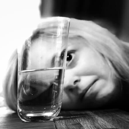 Woman lokking at a glass of water